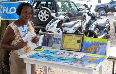 Selma by her stall near the almond tree car park, with a few of her latest books.
